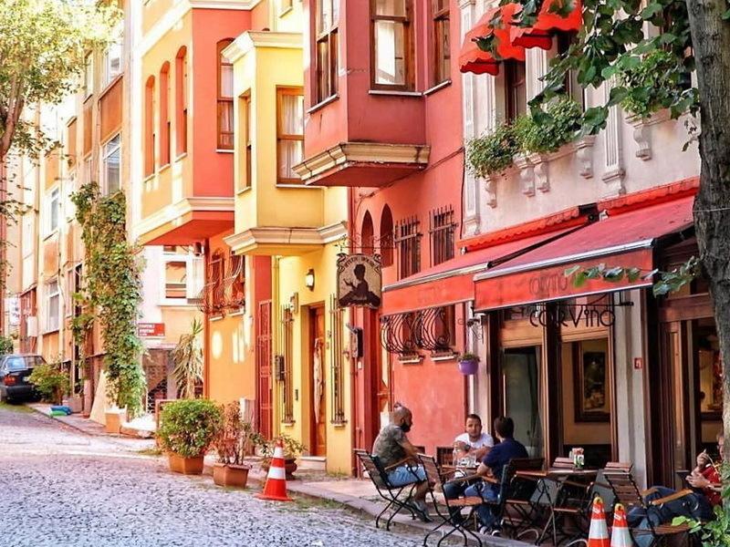 Kuzguncuğun renkli evleri ve bir kafede oturanlar