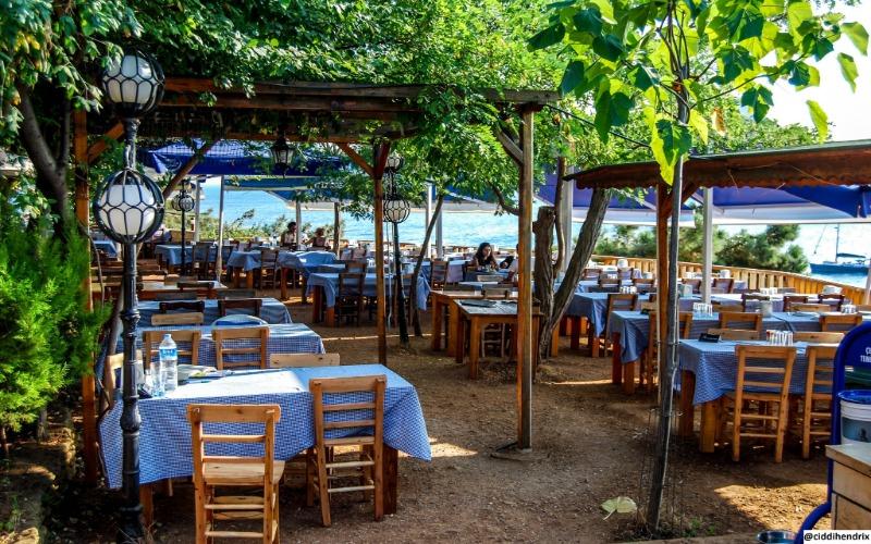 Burgazada yeşillikler arasındaki Kalpazankaya Restoran'ın mavi masa örtülü ahşap masaları ve sandalyeleri